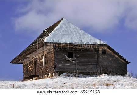 Abandoned wooden cottage in wintry view