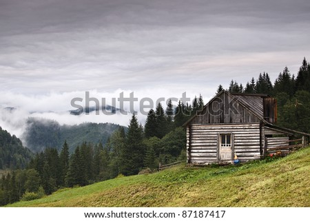 Abandoned wooden house at mountain hill - stock photo