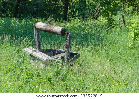 Abandoned wooden old well amidst lush grass on a green meadow