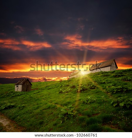 abandoned wooden shacks on the hill and sunset clouds dark and orange - stock photo