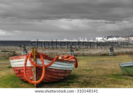 abandonned fishing boat with rope and scenic view of village of Mont Ste-Anne, Quebec, Canada - stock photo