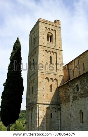 Abbey Sant'Antimo in Tuscany, Italy with a cypress tree