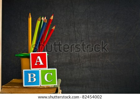 ABC and multicolored pencil on old textbook against blackboard in class. School concept