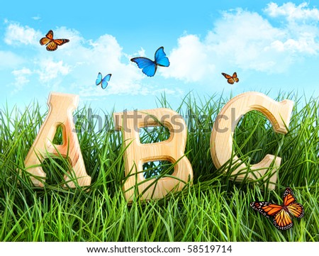 ABC letters in the grass with butterflies - stock photo