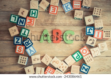 ABC word in wooden block alphabet lay on wooden floor in circle shape