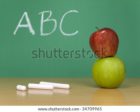 ABC written on a chalkboard. Some chalks and a red apple over a green one on the foreground.