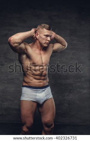 Abdominal shirtless man in a white panties hold his arm over head.