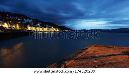Aberdovey, Wales, UK at night, illuminated village next to harbour at night, with jetty in foreground - stock photo