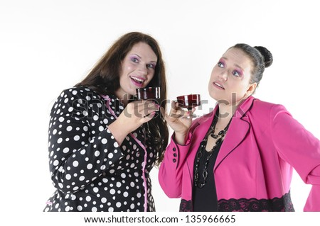 About two faithfully models wear flashy costumes and talking with a mouthful of liquor, isolated against white background.
