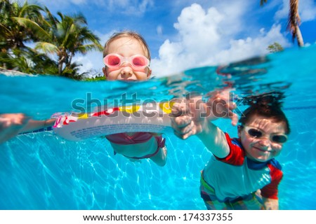 Above and underwater photo of kids swimming in pool - stock photo