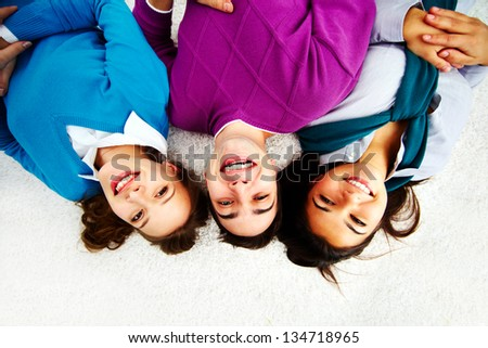 Above angle of attractive friends looking at camera while lying on the floor - stock photo