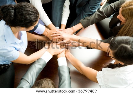 Above angle of business partners making pile of hands on workplace - stock photo
