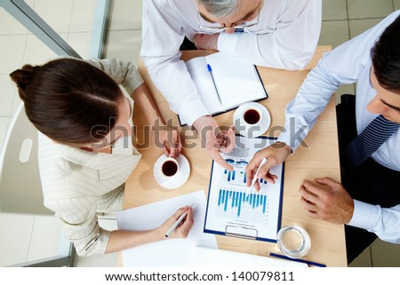 Above angle of business team discussing business document at meeting - stock photo