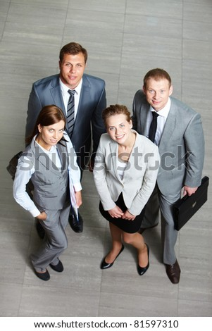 Above angle of confident business group looking at camera - stock photo
