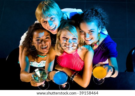 Above angle of happy friends cheering up while handsome guy embracing girls - stock photo