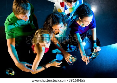 Above angle of happy friends in the bar at party - stock photo