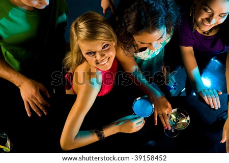 Above angle of happy girl looking at camera with her friends near by in the bar