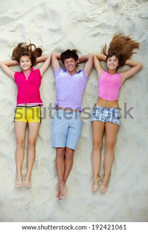 Above angle of happy teenage friends lying on sandy beach - stock photo