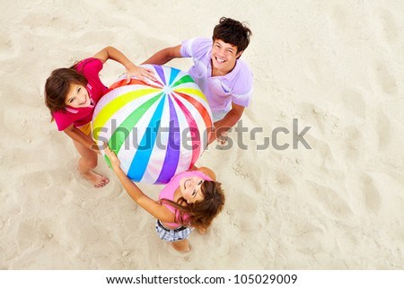 Above angle of happy teenage friends with multi-colored ball looking at camera
