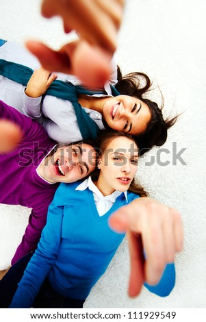 Above angle of teenage friends pointing and looking at camera - stock photo