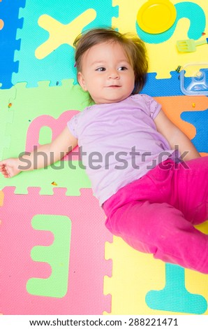 Above angle shot of adorable baby girl lying on child friendly floor mats looking up - stock photo