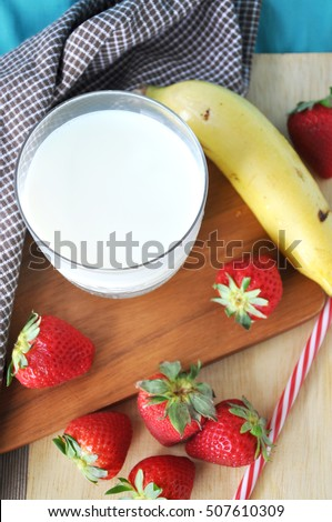 Above of glass of milk with fresh fruits on wooden board
