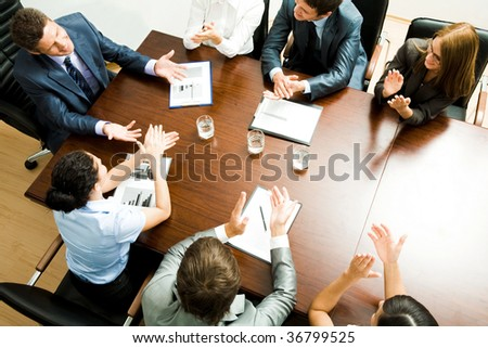 Above shot of happy business partners applauding to confident leader at meeting - stock photo