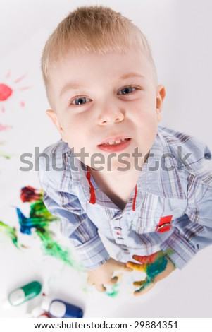 Above shot of preschooler with painted hands looking at camera