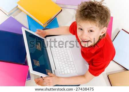 Above shot of smart schoolkid with laptop looking upwards at camera - stock photo