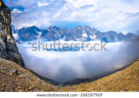 Above the clouds in the mountains. Picture was taken during a trekking hike in gorgeous Caucasus mountains, Bezengi region, Kabardino-Balkaria, Russia.  - stock photo