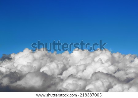 Above the puffy clouds over blue sky - stock photo