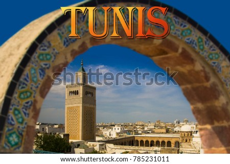 Above the roofs of the Medina (old town) of Tunis. Archway with painted tiles and view of The high minaret of the Great Mosque