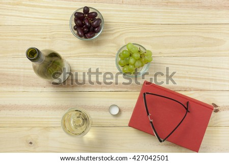Above view of a book on a wooden table with reading glasses, wine bottle and a glass of wine and bowls of grapes - stock photo
