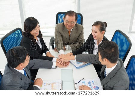 Above view of a business team with a pile of hands in sign of support and togetherness