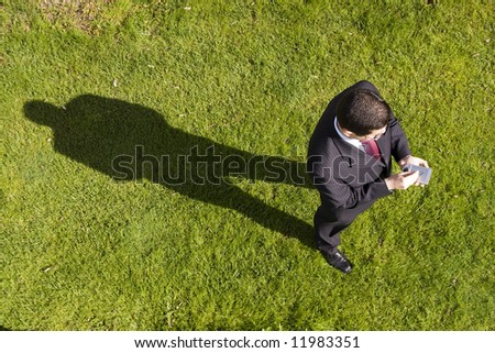 above view of a businessman working with a palmtop (focus on the device) - stock photo