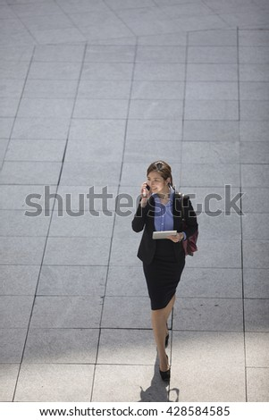 Above view of a happy Asian Businesswoman walking on city street using a smart phone. - stock photo