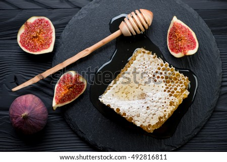 Above view of a honeycomb, liquid honey and sliced figs