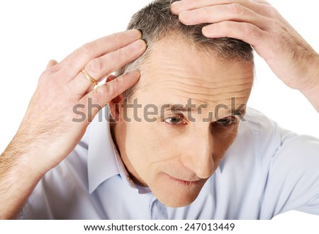 Above view of a man examining his hair. - stock photo