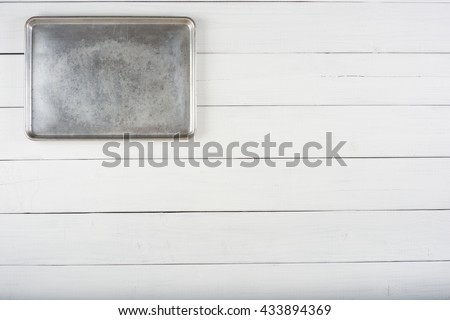 Above View of a Metal Cookie Sheet Cooking Pan Laying or Hung on the top side of a Rustic White or Gray Wood Board Background with room or space for copy, text, your words or ideas. Horizontal photo.