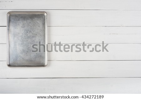 Above View of a Metal Cookie Sheet Cooking Pan Laying or Hung Vertical on the top side of a Rustic White Gray Wood Board Background with room or space for copy, text, your words or ideas.Horizontal.