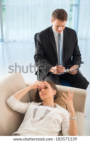 Above view of a patient and doctor, patient explaining problems with emotions while psychologist making notes  - stock photo