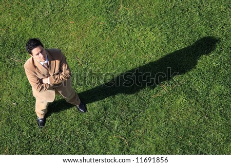 Above view of a serious business man with his shadow on the grass - stock photo