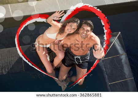 Above view of a smiling couple waving at the camera against heart - stock photo