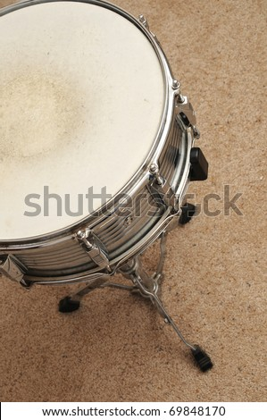 Above view of a snare drum on a stand on a carpet. - stock photo