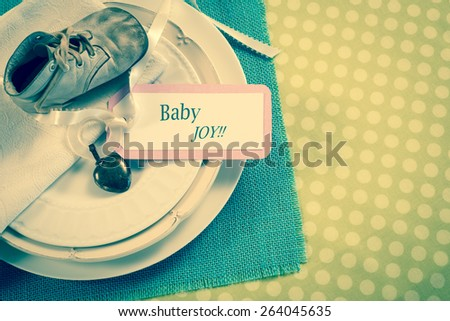 Above View of a Vintage Baby Shoe and Teething Ring and Note Card on table place setting background room or space for copy, text, your words.  Horizontal old fashion, retro trendy, faded instagram  - stock photo