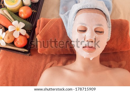 Above view of a young woman in a spa making face mask treatment - stock photo