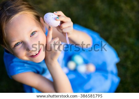 Above view of adorable little girl playing with colorful Easter eggs outdoors on a grass at spring - stock photo