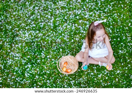 Above view of adorable little girl wearing bunny ears playing with Easter eggs on a grass covered with white flower petals on spring day - stock photo