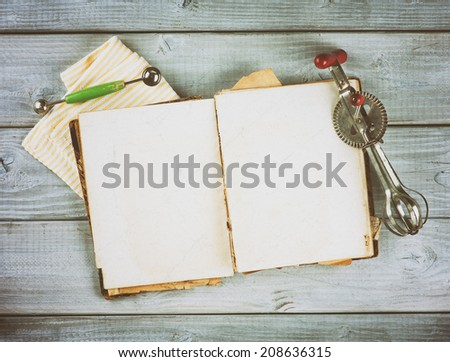 Above View of Antique Recipe Book with background room or space for text, copy, words. Vintage hand mixer and melon baller utensils. Vignette horizontal on textured gray wood boards, instagram - stock photo