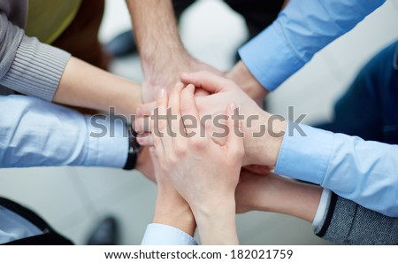 Above view of business partners making a pile of hands  - stock photo